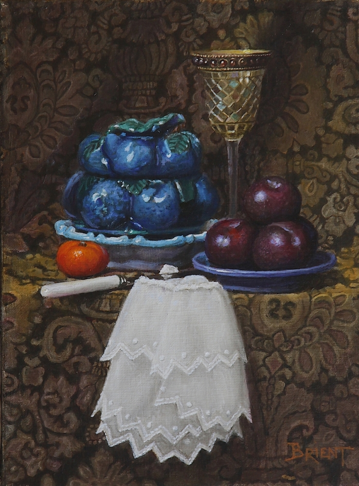 A Covered bowl of blue barbotine, a glass made of mosaiic, a plate of dark plums, a clementine on a pattern fabric