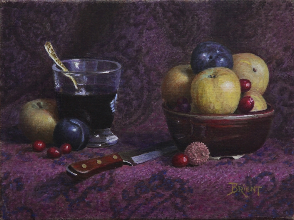 A Bowl of of yellow apples and other fruits, a litchi, some cranberries, a glass of red wine on a pattern fabric