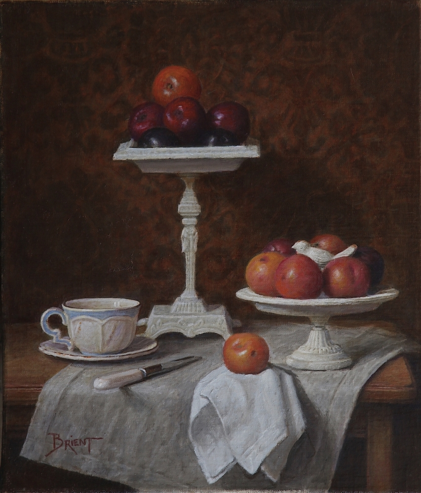 Two compotiers of plums, a cup of tea on a linen napkin