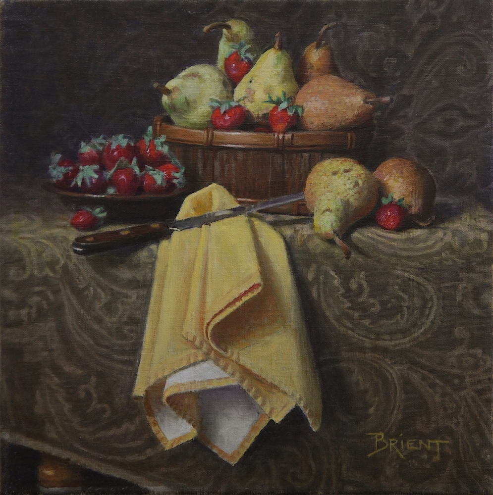 Basket of pears and strawberries, a plate of strawberries, a large yellow napkin, on a pattern fabric