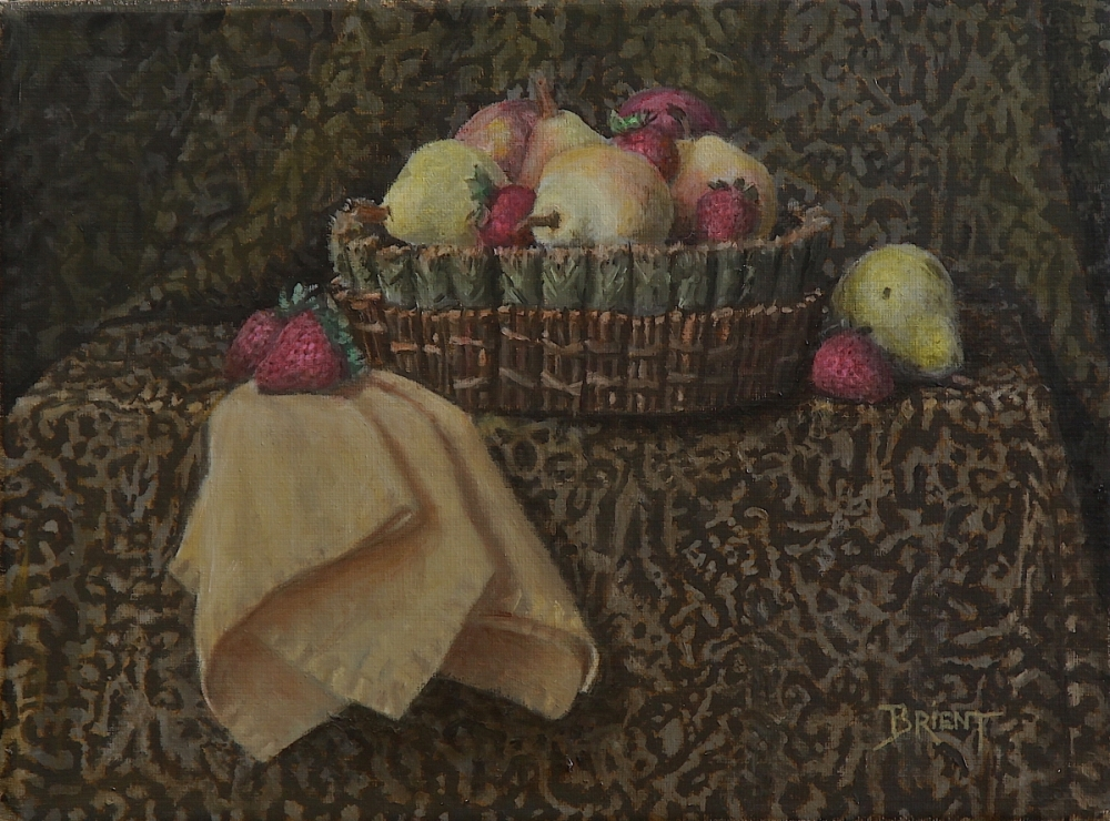 A Basket of yellow pears and strawberries, a yellow napkin on a pattern fabric