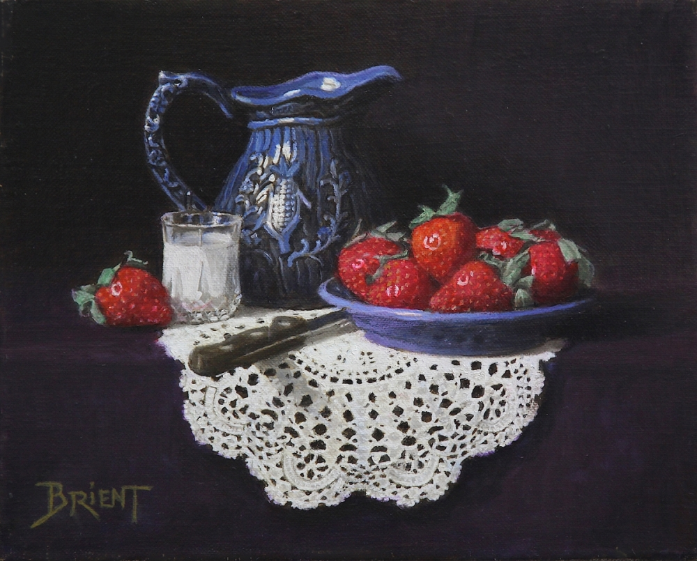 Small blue pitcher, a plate of strawberries, a small glass of milk  on a lace doily