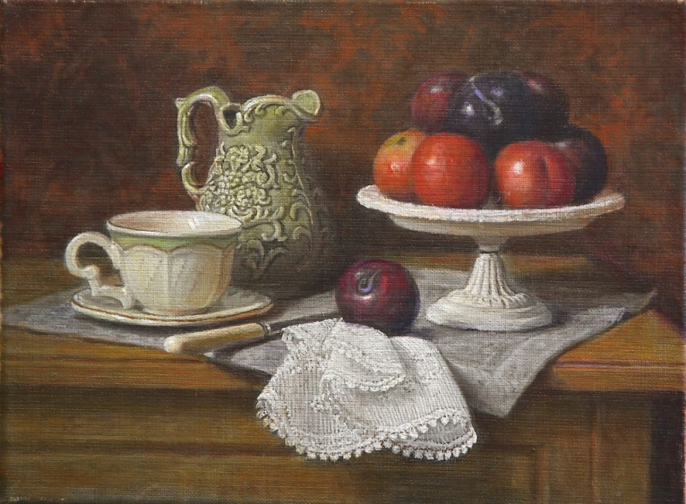 A small green pitcher with a plate of plums and a cup