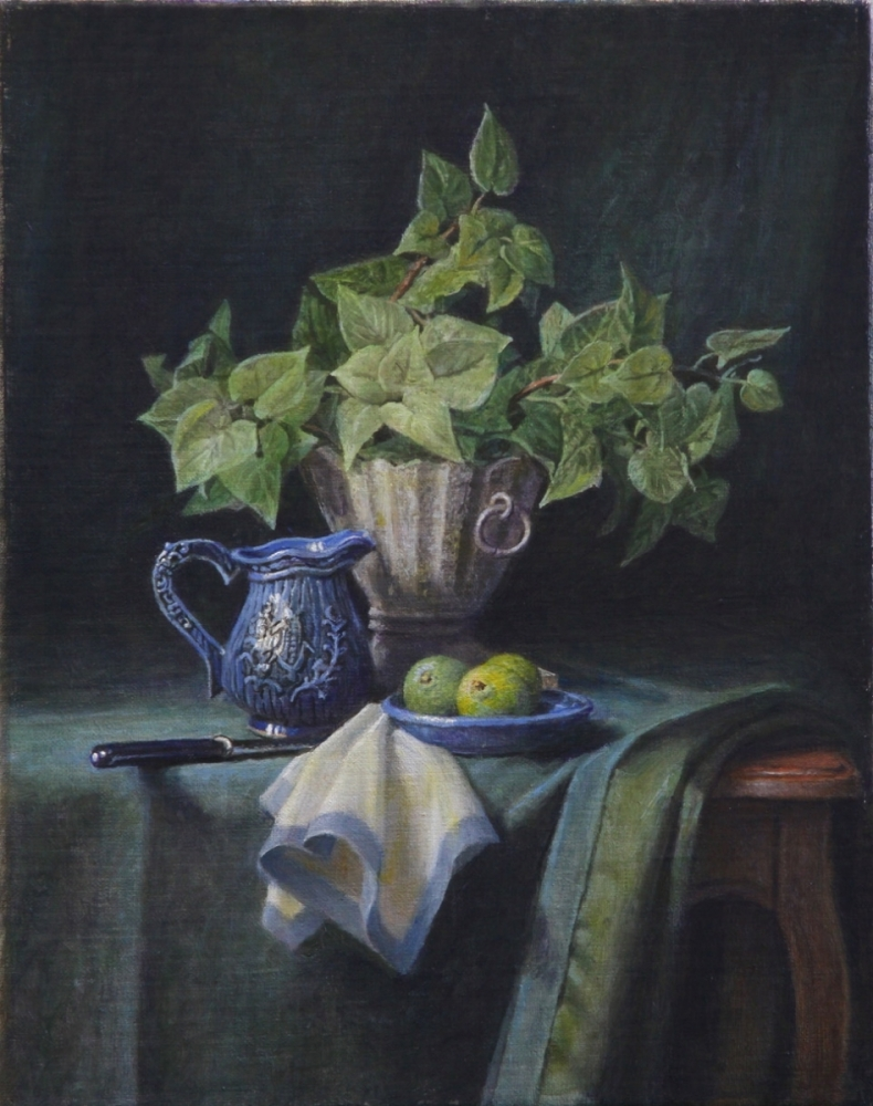 A green plant, a plate of limes a small blue jug