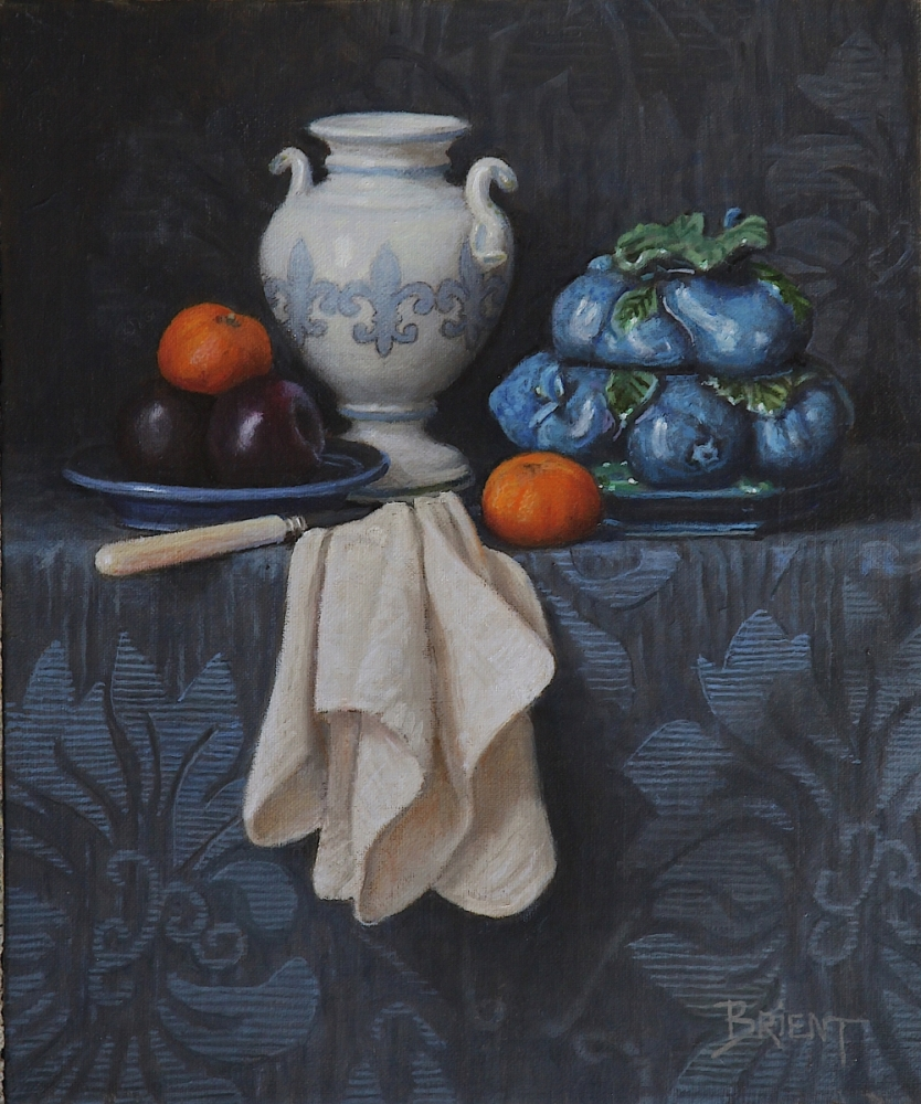 A white vase, a blue ceramic bowl, a plate of plums, two clementines